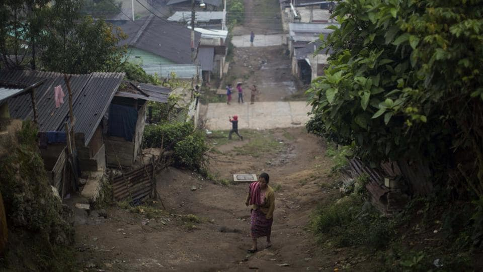 A woman walks up an unpaved road in the Ixil Mayan village of Santa Avelina.Today little has changed in Santa Avelina and poverty here is still extreme. Wood and sheet metal homes dot the hillsides, while others have been upgraded with block construction.  (AP)
