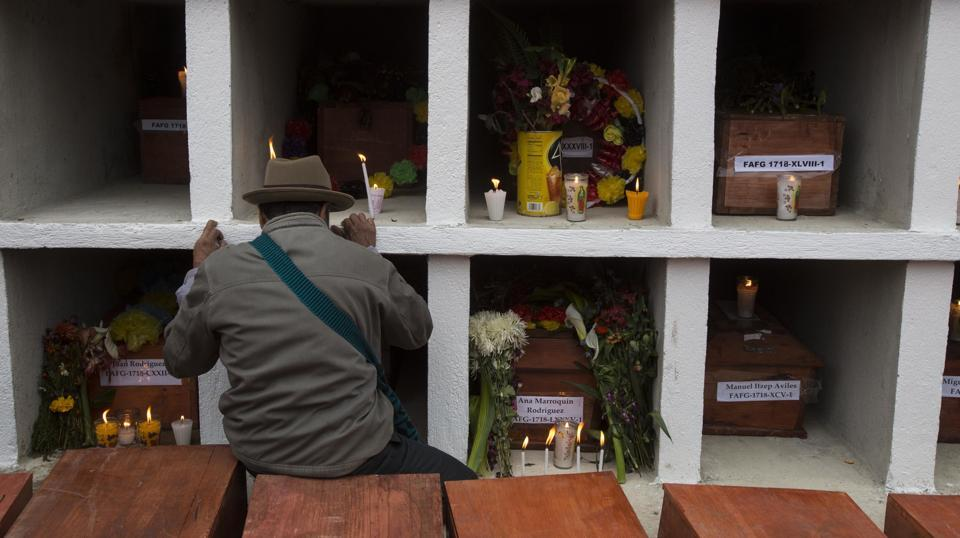 An Ixil Maya man prays next to the niches  in Santa Avelina cemetary. Since the exhumations began, experts have identified 108 of the victims through DNA testing or through personal objects recognized by family members. The return of the bodies has given relatives a place to bring flowers and light candles as per tradition. (AP)
