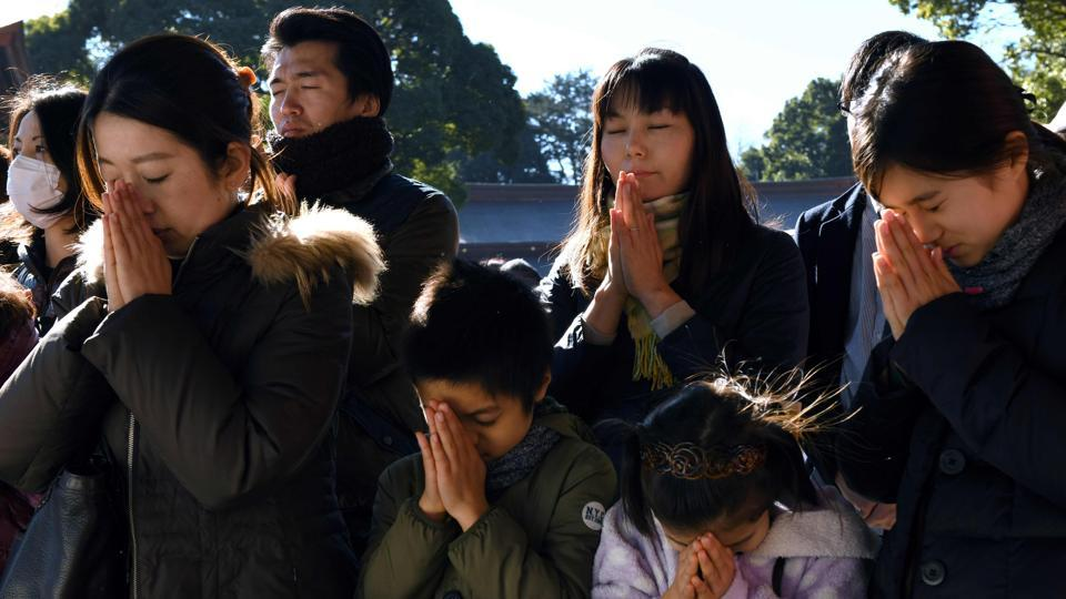 Worshippers pray during a New Year's Day visit to Meiji shrine in Tokyo on January 1, 2018. Millions of Japanese people visit shrines and temples across the country during the first three days of the new year to pray for the well-being of their families. (Kazuhiro Nogi / AFP)