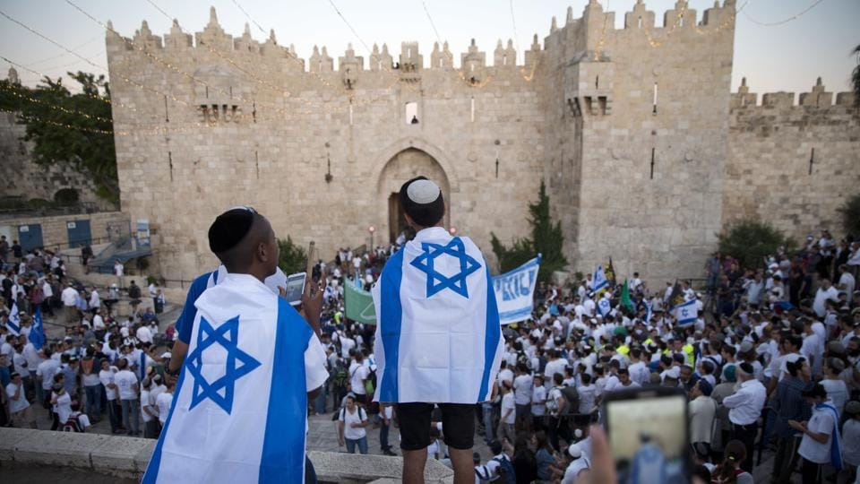 Israelis carry national flags outside the Old City's Damascus Gate in Jerusalem, during Jerusalem Day which marks the 50th anniversary of Israel's capture of the city's eastern half from Jordanian control during the Six-Day War in 1967.  (Oded Balilty / AP)