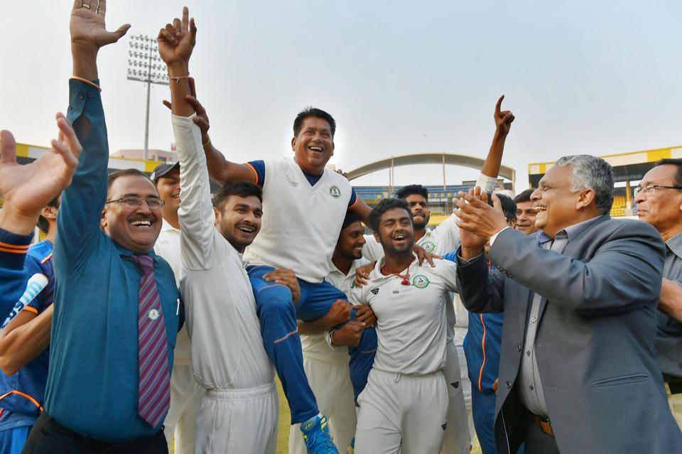 Vidarbha players celebrate with their coach Chandrakant Pandit after winning the Ranji Trophy final cricket match against Delhi, January 1.