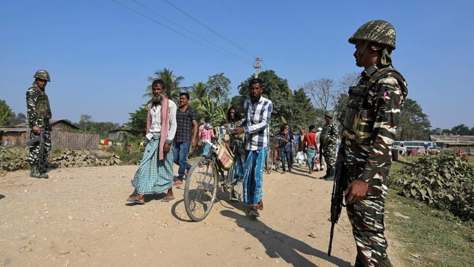 Villagers walk past Central Reserve Police Force (CRPF) personnel patrolling a road ahead of the publication of the first draft of the National Register of Citizens (NRC) in the Juria village of Nagaon district in Assam, on December 28, 2017.
