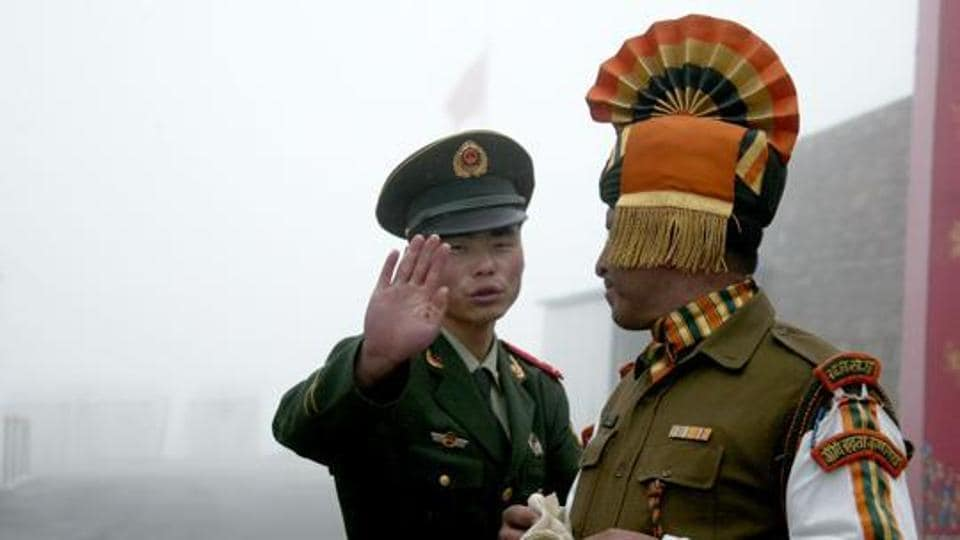 A Chinese soldier gestures next to an Indian soldier at the Nathu La border crossing between India and China in Sikkim.