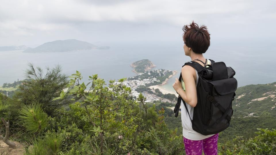 A female hiker enjoys the view on the famous Dragon's Back Trail in Hong Kong.