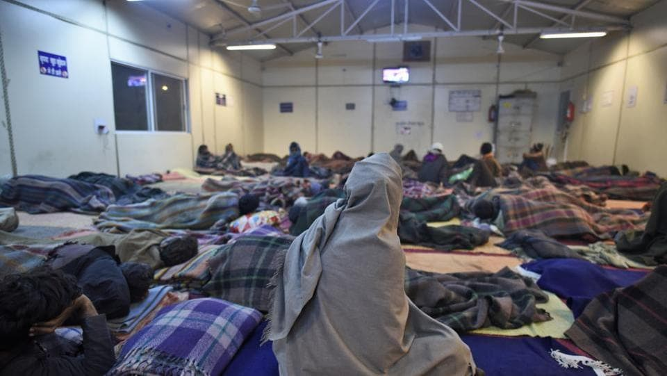 Of Delhi's approximately 20,000 homeless men, women and children, around 13,000 stay in these mat-lined shelters across the city. The movie screening had been organised as part of a New Years' Eve celebration for them.  (Burhaan Kinu / HT Photo)
