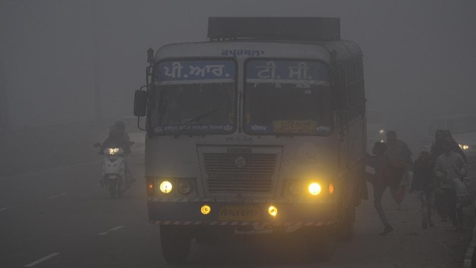 Passengers boarding a bus in dense fog on the out skirts of Jalandhar on Tuesday.