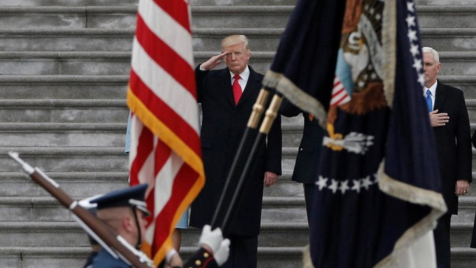 US President Donald Trump salutes as he presides over a military parade.