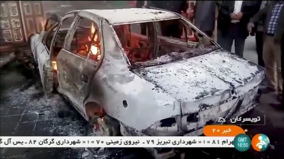 "People stand near a burning car in Tuyserkan, Iran on December 31, 2017. The Fars news agency reported ""scattered groups"" of protesters in Tehran on Monday. Unsigned statements on social media urged Iranians to continue to demonstrate in 50 towns and cities. The government has said it was temporarily restricting access to Telegram and Instagram apps with reports that internet mobile access was also hit in some areas.  (IRINN / REUTERS)"