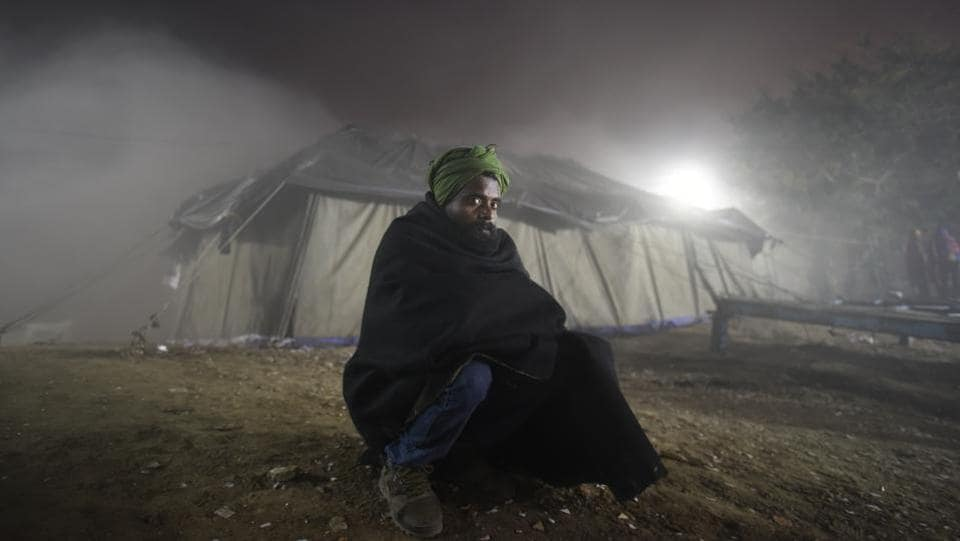 A homeless person huddles in a temporary open air theatre screening a movie on New Year's Eve near Nigambodh Ghat. The choice of movie didn't necessarily cater to everyone's taste but a chance to watch one on a big screen was draw enough to step out in the biting cold. (Burhaan Kinu / HT Photo)
