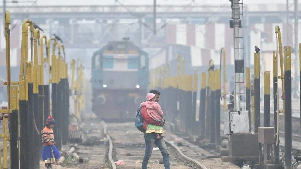 A man crosses a railway track on a cold and foggy morning in Lucknow on Monday.