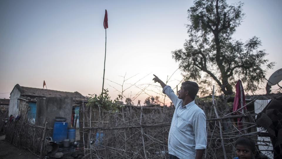 But now both sides are working together to prevent attacks. A man points towards a red flag placed by the forest department as a sign of tiger presence in the area and need for caution. Villagers are paying heed to such warnings and taking measures of their own. (Pratik Chorge / HT Photo)