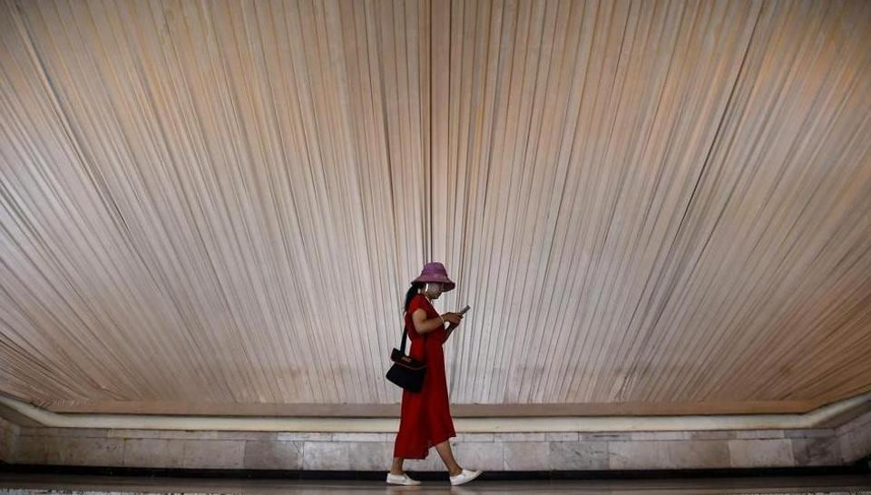 A woman looks at her phone as she walks inside an exhibition centre in Shanghai.