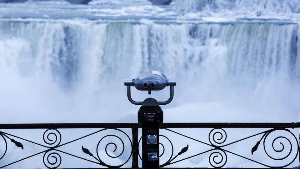 Binoculars look over ice forming at the base of the American Falls as viewed from Ontario. Much of the eastern United States is gripped by a sustained cold spell that has played havoc with public works causing pipes to freeze and water mains to burst, and impeded firefighting as temperatures barely crossed -6 degrees Celcius. (Aaron Lynett / The Canadian Press via AP)