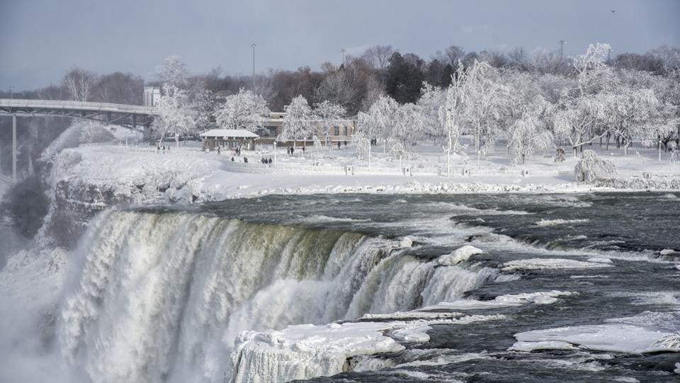 The frozen over American Falls and Prospect Point are seen from Goat Island on the American side. The westerly wind usually blows the mist toward the US side where the condensation wraps every inch of the landscape. (James Neiss / The Niagara Gazette via AP)