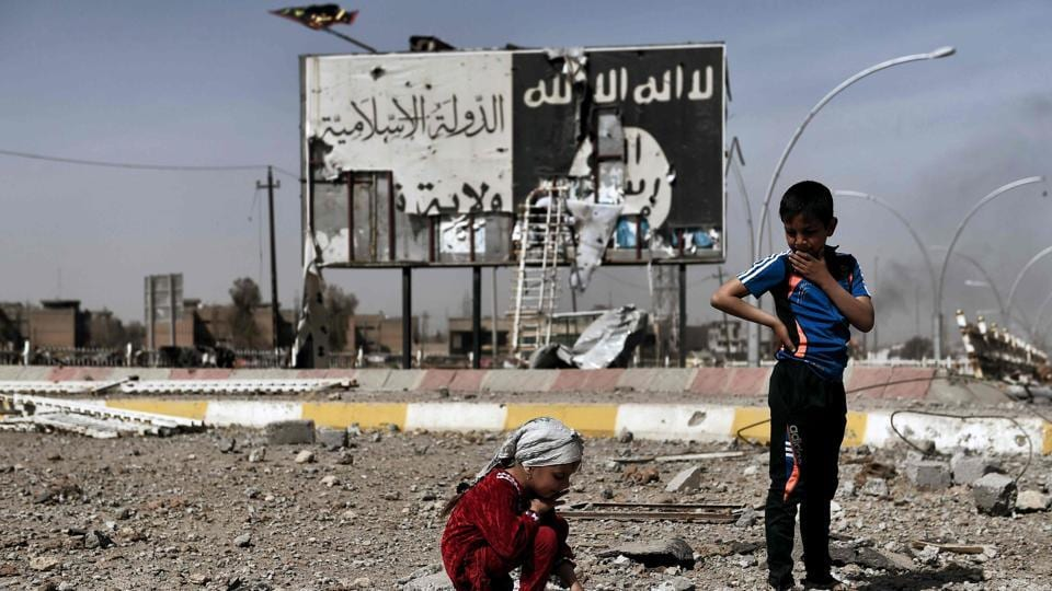 This file photo taken on March 12, 2017 shows Iraqi children sitting amidst the rubble of a street in Mosul's Nablus neighbourhood in front of a billboard bearing the logo of the Islamic State (IS) group.