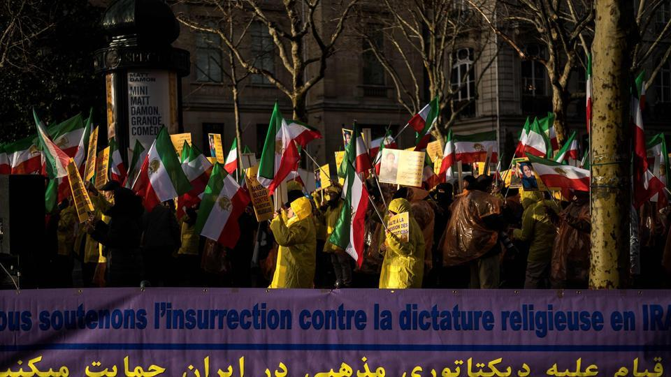 Protesters hold flags of the National Council of Resistance of Iran (NCRI) next to a banner reading