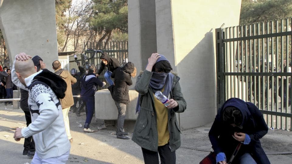 In this photo taken on December 30, 2017, university students run away from stones thrown by police during an anti-government protest inside Tehran University