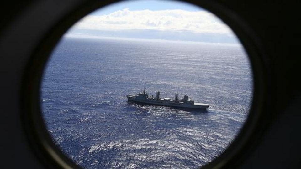 In this March 31, 2014 file photo, HMAS Success scans the southern Indian Ocean, near the coast of Western Australia, as a Royal New Zealand Air Force P3 Orion flies over, while searching for missing Malaysia Airlines Flight MH370.