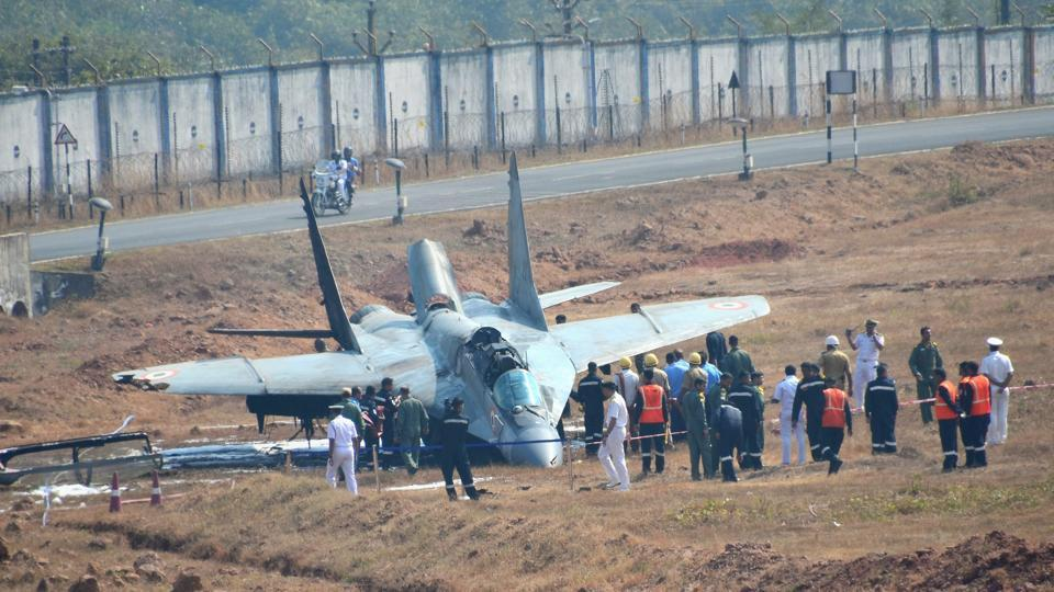 Security personnel standing near the MiG-29 K aircraft of the navy which caught fire after it skidded off the runway in Goa's Dabolim International Airport on Wednesday. (PTI)