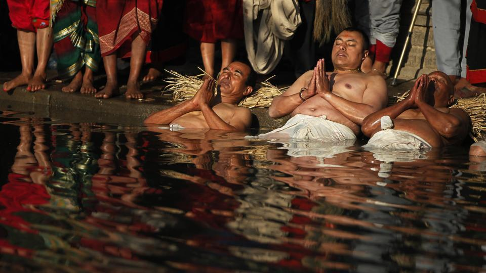 Men perform a half dip in the Hanumante River. During the month-long festival hundreds of thousands of Hindus are expected to take these dips in the holy waters on astronomically auspicious days, to pay tribute to goddess Swasthani, who is believed to bring good fortune. (Niranjan Shrestha / AP)