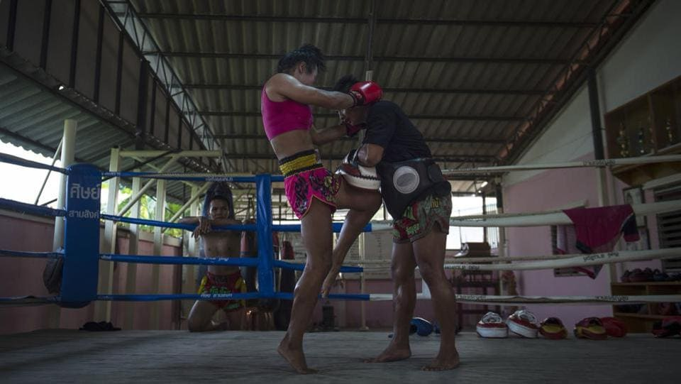 Nong Rose practices knee strikes with her brother. She turned professional after graduating from high school two years ago, pushing through prejudice by racking up victories, winning half of her 300 matches. Today, she is better known for her knees of steel. (Lilian Suwanrumpha / AFP)