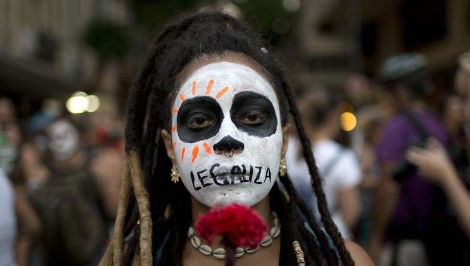 """A woman with the word """"Legalize"""" painted on her mouth marches against a congressional vote to make abortion illegal nationwide, on November 13, 2017 in Rio de Janeiro. Still a taboo, abortion remains illegal in Brazil with few exceptions. But amid a rising tide of conservatism and concerns against further restrictions, women are coming out of the shadows to share their stories in hopes of galvanizing support. (Silvia Izquierdo / AP)"""