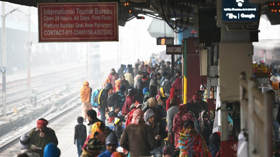 Those stranded huddled themselves in blankets and thick shawls, slept on benches or indulged in cards games to while away time as the New Delhi Railway stations' platforms coped with almost 100 trains running up to 30 hours late.  (Sanchit Khanna / HT Photo)