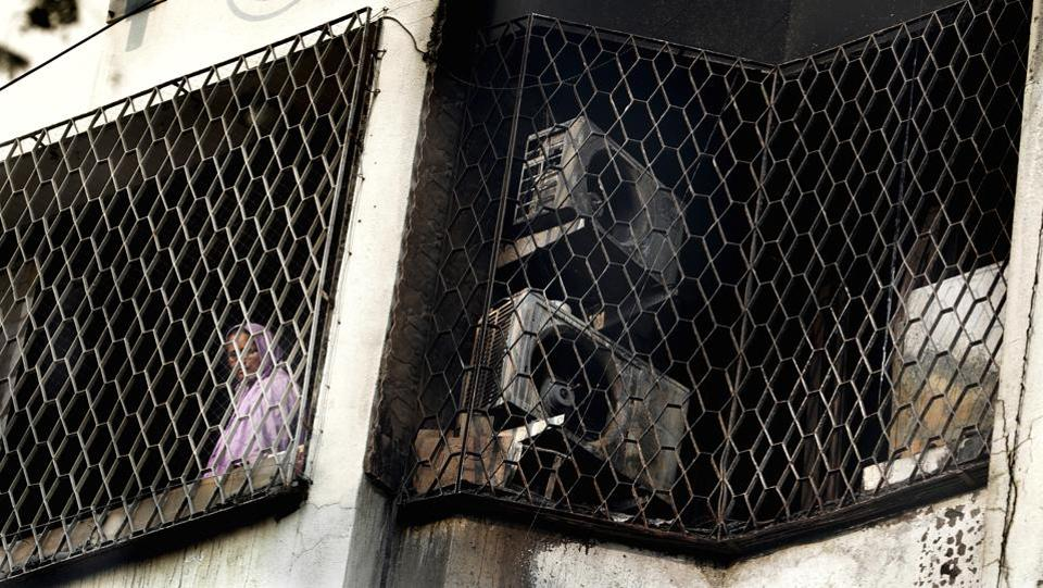 A woman looks out from the window of a residential building in Mumbai's Andheri East after it was partially damaged in an early morning fire which claimed the lives of four people, including two children and left five injured. (Rafiq Maqbool / AP)