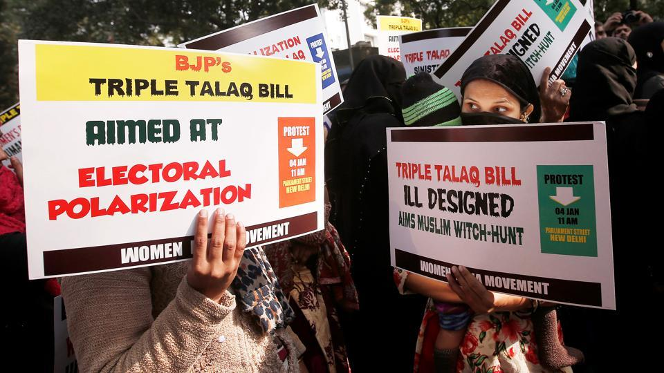 Muslim women hold placards during a protest against a bill passed by the Lok Sabha last week that aims at prosecuting Muslim men who divorce their wives through triple talaq.