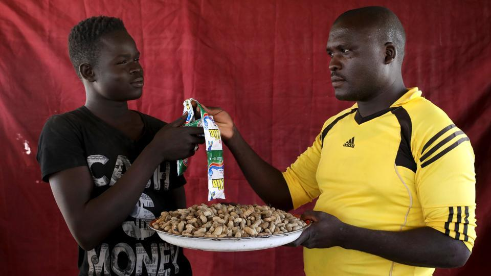Nasiru Buba (R) exchanges detergent for a tray of groundnuts at the Bakasi camp. Buba was trading packets of laundry detergent which he had bought after working as a porter in the city and wanted to trade them for groundnuts. Buba said the groundnuts were for his wife who had just delivered a baby. (Afolabi Sotunde / REUTERS)
