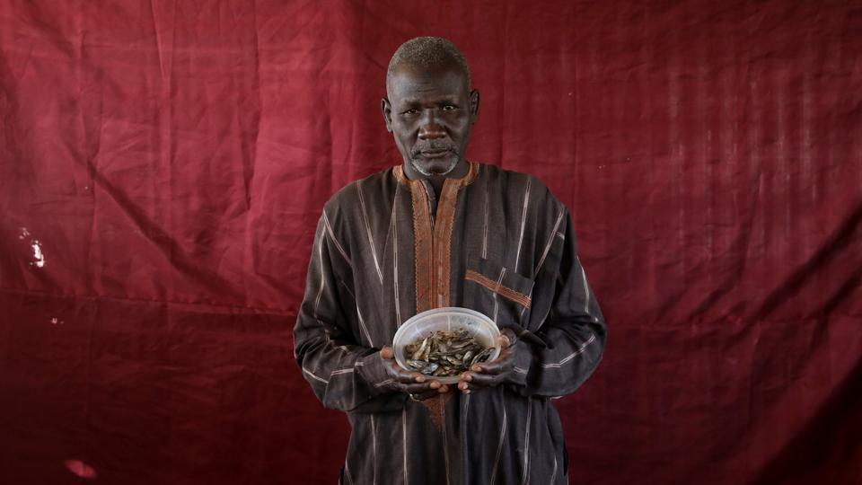 Abdulwahal Abdulla, a 50-year-old living in Bakasi for three years, hoped to trade his bowl of young tilapia worth roughly 150 naira for cooking oil. The dusty Bakasi camp sits on the outskirts of the city of Maiduguri in Borno, the spiritual home of the Islamist Boko Haram movement, which wants to establish a caliphate in the region surrounding Lake Chad. (Afolabi Sotunde / REUTERS)