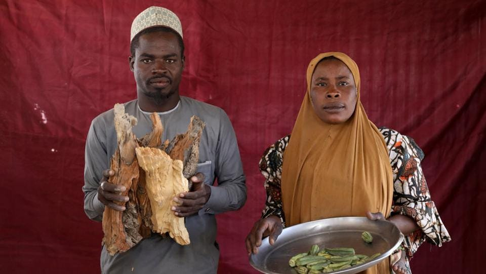 Isa Zakariya Audu (L), holds pieces of firewood whilst Kakaye Ahmadu Maikifi holds up a plate of okra. More than 670,000 live in camps in Nigeria's northeast, where cash is hard to come by, opportunities for work are rare and the food and aid they receive is often not what they want. (Afolabi Sotunde / REUTERS)