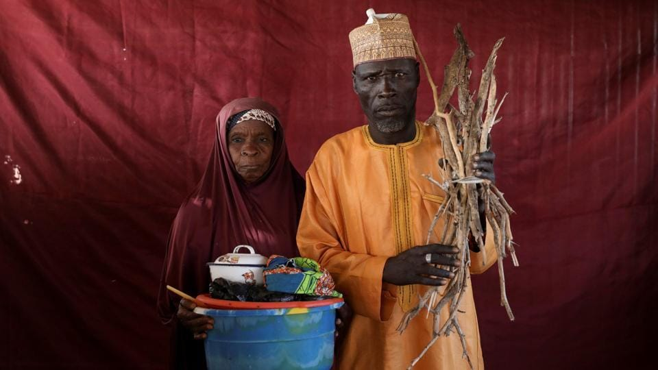 Aisha Umaru (L) holds a basin of milk as Umari Usman Kaski holds up firewood in Nigeria. Many of those responding to the crisis are also concerned that with economic prospects dim for the foreseeable future, millions of people will become dependent on the aid, the vast majority of which comes from abroad. (Afolabi Sotunde / REUTERS)