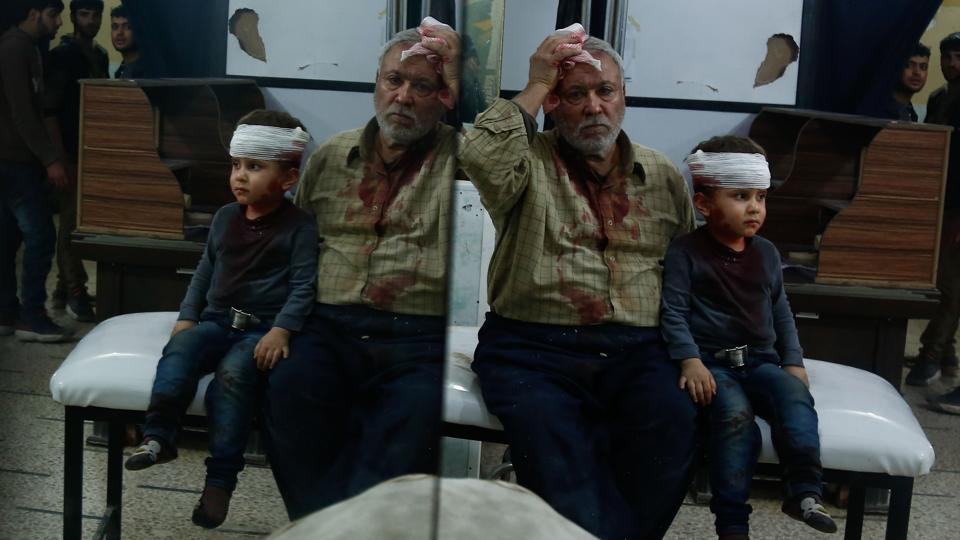 A Syrian man and a child, who were injured in shelling on the town of Misraba, receive treatment at a makeshift hospital in the besieged rebel-held town of Douma, on the outskirts of the capital Damascus early Thursday.