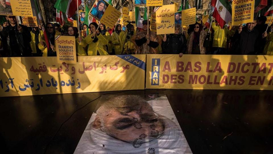 Protesters in Paris on Wednesday hold placards as they stand behind a portrait of Iranian President Hassan Rouhani during a demonstration in support of the Iranian people amid a wave of protests spreading throughout the country.