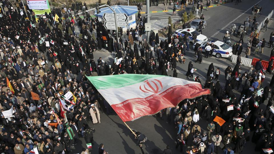 A demonstrator waves a huge Iranian flag during a pro-government rally in the northeastern city of Mashhad on Thursday.