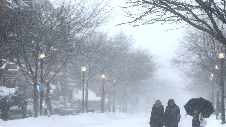 Pedestrians walk down a vacant Newbury Street during a massive winter storm in Boston, Massachusetts.  (AFP)