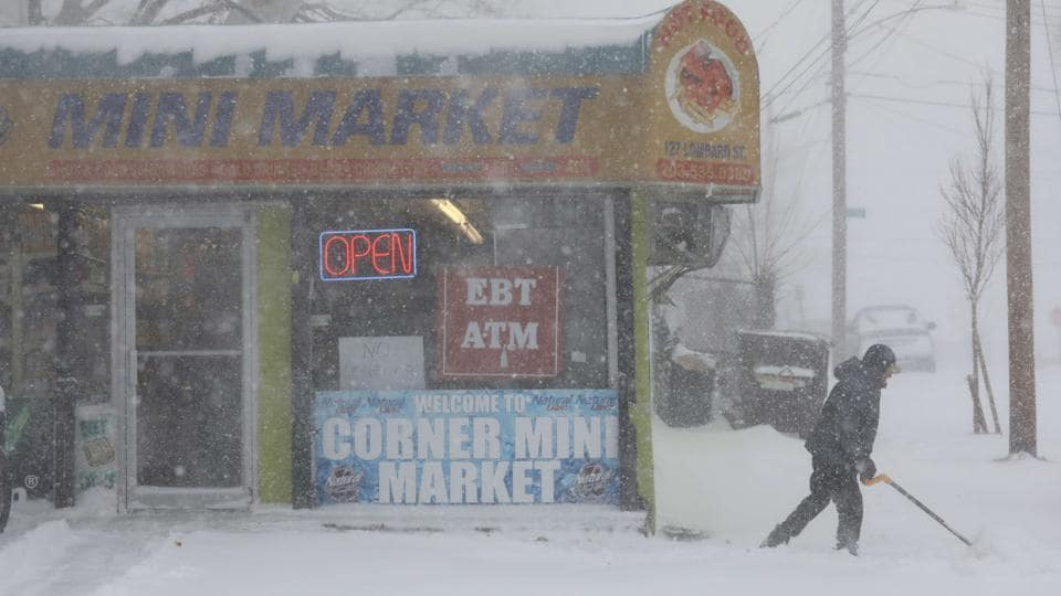 A shopkeeper shovels snow in New Haven, Connecticut. The only nuclear plant in Massachusetts was shut just after 2 pm because of the failure of a line that connects the reactor to the power grid. ISO New England, which operates the region's power grid, attributed the shutdown to blizzard conditions. The company did not say when the station would restart. (John Moore / Getty Images / AFP)