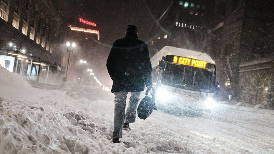 A man walks through the snowed out streets of Boston on Thursday. The area received 12 inches of snow, with more on the way, according to the National Weather Service and parts of New Jersey were also buried under nearly a foot and a half. (Spencer Platt / Getty Images / AFP)