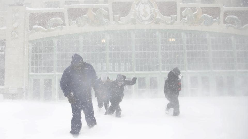 People leave the Paramount Theater after stopping by the beachfront building to sightsee the Atlantic Ocean during the winter snowstorm on Thursday in New Jersey. The region has also been in the grip of a prolonged cold spell. Prices for heating oil and natural gas in the US Northeast hit their highest levels in years on the back of near-record heating demand. (Julio Cortez / AP)