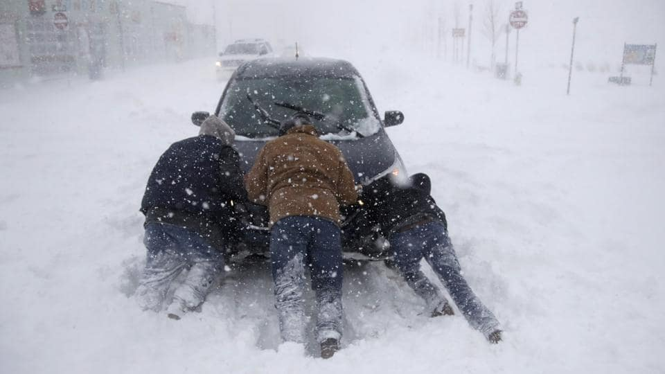 A group of men help a motorist after his car was stuck in the snowstorm near Asbury Park, New Jersery. Four people were reported killed in the southeastern states of North and South Carolina, where icy roads sent vehicles skittering. A cold wave gripping a large section of the United States had already been blamed for a dozen earlier deaths. (Julio Cortez / AP)