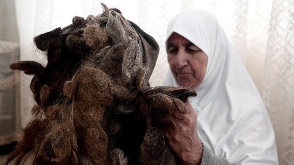 Ezzeya Daraghmeh, an 82-year-old Palestinian who claims she has kept locks of her hair over 67 years, holds her collected hair as she stuffs it in a pillow, on January 2, 2018 in the West Bank town of Tubas. (Raneen Sawafta / REUTERS)