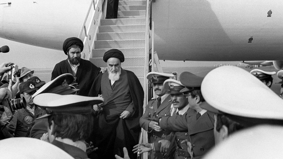 This file photo taken on February 01, 1979 at Tehran airport shows Iran's Ayatollah Ruhollah Khomeini (C) leaving the Air France Boeing 747 jumbo that flew him back from exile in France to Tehran.