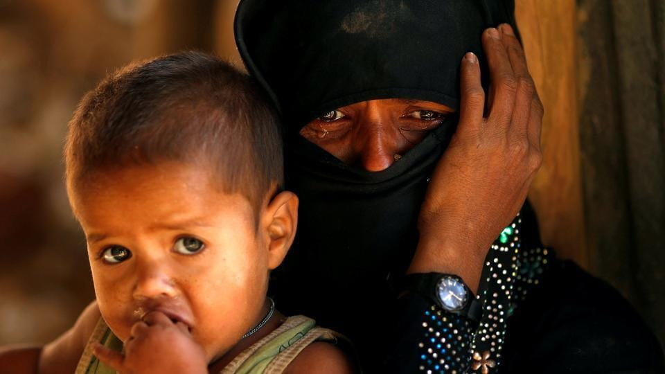 A Rohingya refugee cries next to her son, outside a temporary mosque at Kutupalong refugee camp on January 04 2018 near Cox's Bazar, Bangladesh. (Tyrone Siu / REUTERS)
