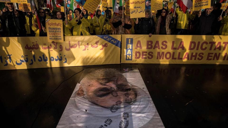 "Protesters hold placards reading ""Support Iranians risen up against the religious dictatorship"" as they stand behind a portrait of Iranian President Hassan Rouhani with shoe marks over it during a demonstration on January 03, 2018 in Paris, France. (Lionel Bona Venture / AFP)"