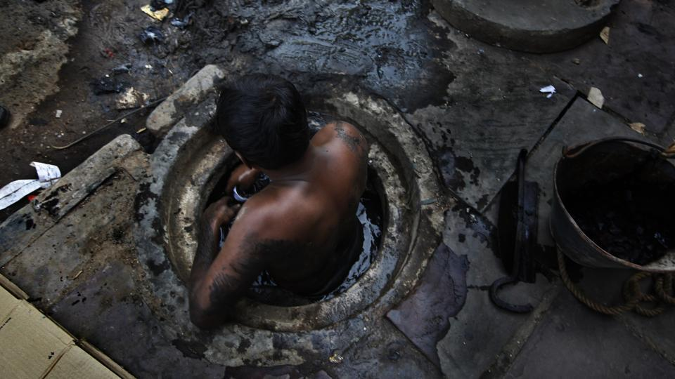 A  municipal workers  attempts to unblock a sewer overflowing with human excreta in New Delhi.