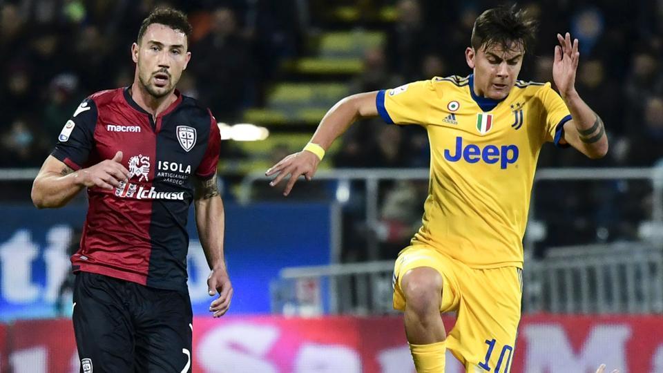 Juventus forward Paulo Dybala vies with Cagliari midfielder Nicolo Barella during their Italian Serie A  encounter.