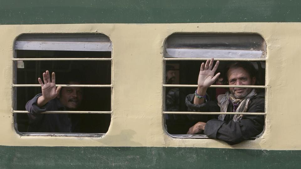 Indian fishermen wave to journalists from a train as they leave for their homeland in Karachi on Sunday.