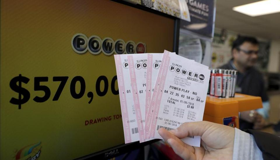 A customer shows her purchased Powerball tickets at a convenience store Saturday, Jan. 6, 2018, in Chicago. The jackpot jumps to an estimated $570 million for Saturday's drawing. That would make it the nation's 8th largest lottery prize ever.