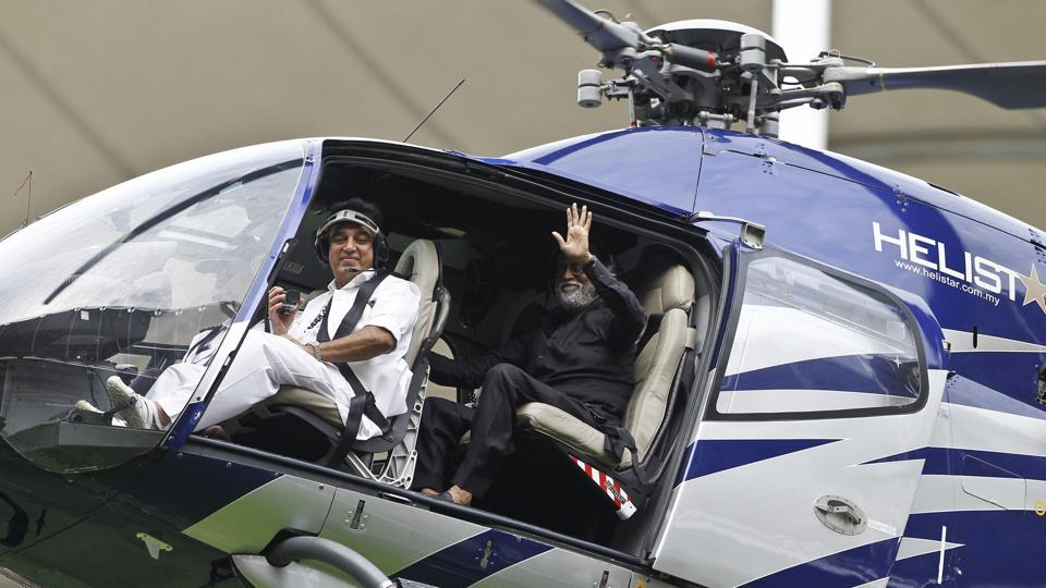 Superstars Kamal Haasan and Rajinikanth wave to the fans as they arrive at an event in Kuala Lumpur, Malaysia, on Saturday.